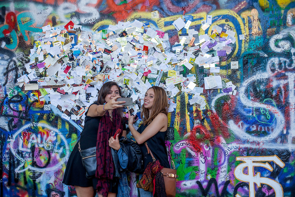 Tourist photograohing a selfie at The Lennon Wall or John Lennon Wall, which is a wall in Prague, Czech Republic. Once a normal wall, since the 1980s it has been filled with John Lennon-inspired graffiti and pieces of lyrics from Beatles songs.
