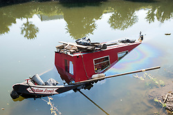 """© Licensed to London News Pictures; 16/09/2020; Bath, UK. The canal boat """"Indian Scout"""" is seen partly submerged on the river Avon in Bath. Canal boats were evacuated and some boats sunk on the river Avon at Twerton after the sluice gates failed yesterday evening (15 September) and the water level dropped dramatically. The Fire Service assisted. The Canal and River Trust have issued a statement saying a drop in water level on the River Avon was caused by a failure of the Environment Agency's sluice gates and that the sudden and dramatic drop in levels meant that it was impossible to give warning to the boaters. The Canal and River Trust say they understand the difficulties faced by the EA in repairing the sluice and this is the second time this has happened, so they are looking to the EA to find a solution as a matter of urgency.  Photo credit: Simon Chapman/LNP."""