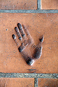 impression of hand print in a red floor tile