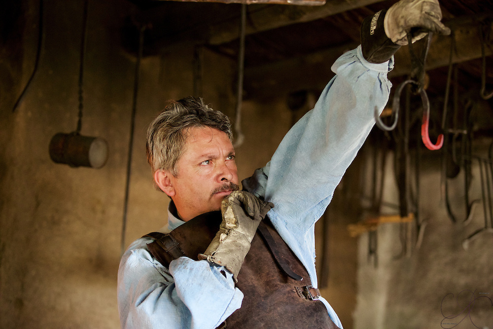 A blacksmith looks over his work to ensure it is up to the task before the metal cools down.
