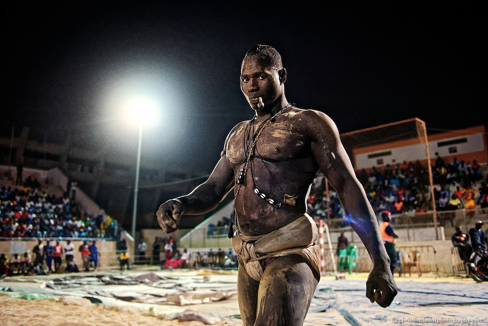 A wrestler warms up before the final fight at the Iba Mar Diop stadium in Dakar on March 29, 2015. So-called Gris-gris are magic amulets which the fighters carry on their bodies or often in their mouths.