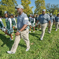 Detroit's Cody High School Varsity football team and cheerleaders march toward the first game on their new field.
