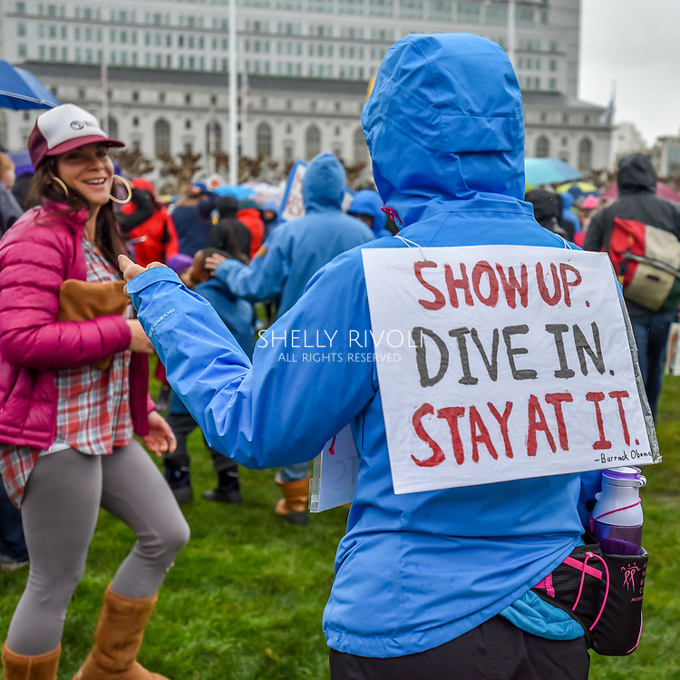 "Not to be thwarted by the rain, a demonstrator at the rally before the first Women's March wears a rain coat topped by a plastic-shielded sign reading, ""Show up. Dive in. Stay at it,"" Obama's words from his presidential farewell."