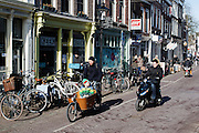 In Utrecht rijdt een man met een kind op een bakfiets door de Twijnstraat. Een jongen op een snorscooter passeert hem.<br /> <br /> In Utrecht a man rides on a cargo bike with a child at the Twijnstraat. A boy on a scooter is passing.