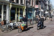 In Utrecht rijdt een man met een kind op een bakfiets door de Twijnstraat. Een jongen op een snorscooter passeert hem.<br /> <br /> In Utrecht a man rides on a cargo bike with a child at the Twijnstraat. A boy on a scooter is passing.