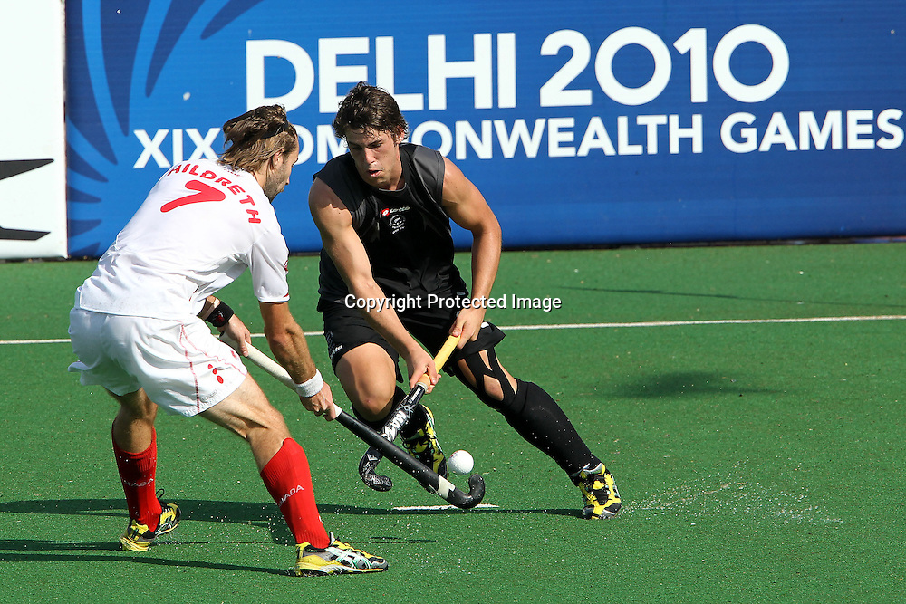 Nick Wilson of Canada takes on Richard Hildreth of Canada during the hockey match between New Zealand and Canada during the XiX Commonwealth Games  held at the MDC Stadium in New Delhi, India on the  10 October 2010<br /> <br /> Photo by:  Ron Gaunt/photosport.co.nz