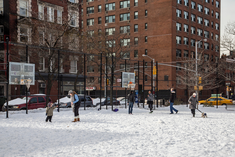 A woman plays with her young child with the snow, behind are three men playing basketball as a woman walks past with her dog just off Husdon Street, New York City,  New York, United States of America.  The whole recreation area is covered in snow after the record breaking snowstorm in January 2016.  (photo by Andrew Aitchison / In pictures via Getty Images)