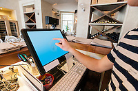 Cropped image of cashier touching computer screen at restaurant counter