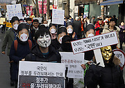 "Wearing masks, people march during an anti-government rally in Seoul, South Korea, December 5, 2015. The ""People's Camp for Rising Up and Fighting"", representing various groups of farmers, students, workers and the poor, demonstrated to oppose South Korean President Park Geun-hye to change the labor market which protesters insist, will allow easier layoff and more temporary workers and to monopolize the authorship of history textbooks. People wore masks at the rally to denounce Park who recently compared local protestors in masks to ISIS. The organizer said 50,000 people participated in the demo, while the police estimated that 14,000 attended. A sign (front R) reads,""We are not IS, we are people"". Photo by Lee Jae-Won (SOUTH KOREA)  www.leejaewonpix.com"