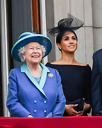 Queen Elizabeth ll and Meghan, Duchess of Sussex stand on the balcony of Buckingham Palace in London to watch the flypast to mark the centenary of the RAF (Royal Air Force)  on July 10, 2018.
