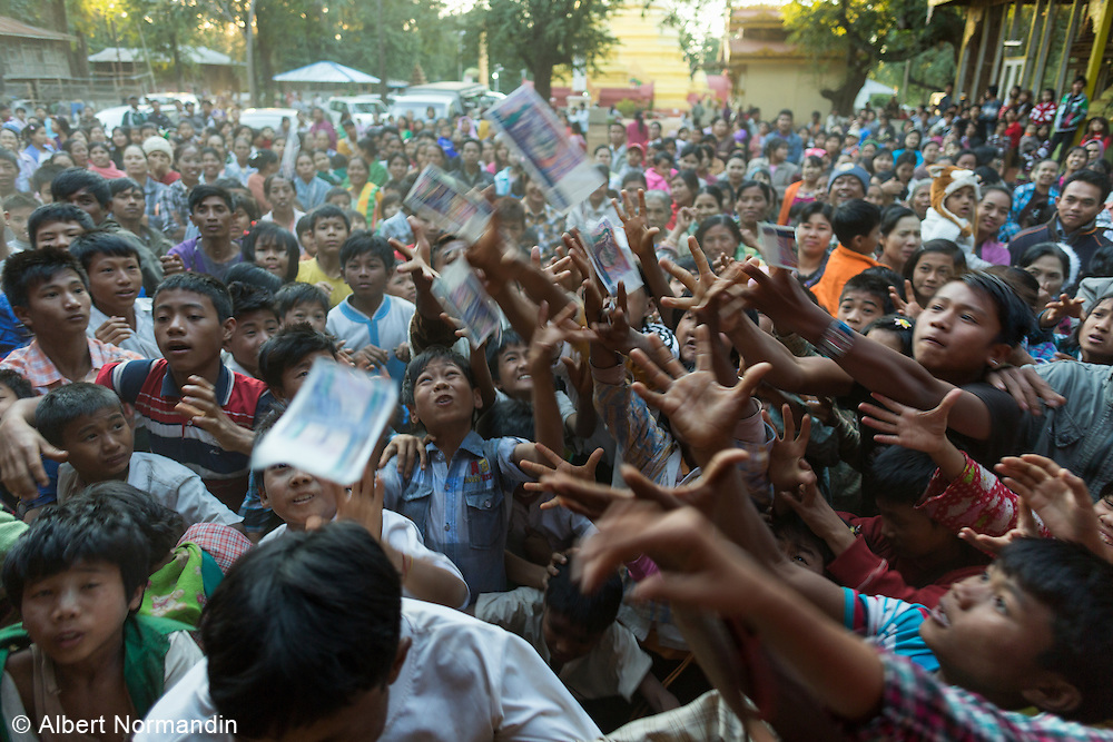 large crowd of people fighting and grabbing Lucky Money being thrown out at Mount Popa Nay Festival