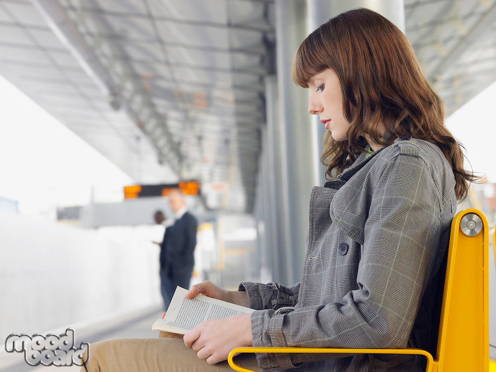 Businesswoman sitting on bench reading a book at Train Station side view