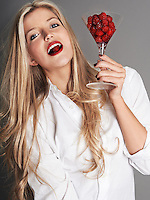 Pretty blonde girl holding glass of raspberries