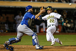 OAKLAND, CA - JULY 15:  Josh Reddick #22 of the Oakland Athletics scores a run ahead of a tag from Russell Martin #55 of the Toronto Blue Jays during the seventh inning at the Oakland Coliseum on July 15, 2016 in Oakland, California. (Photo by Jason O. Watson/Getty Images) *** Local Caption *** Josh Reddick; Russell Martin