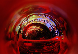 """Beauty at the Bottom: Hell""- This image is a photograph of a beer bottle shot right down the mouth of the bottle. A television provides the main light source."