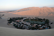 A sunset view of the oasis village of Huacachina from the top of the surrounding dunes.