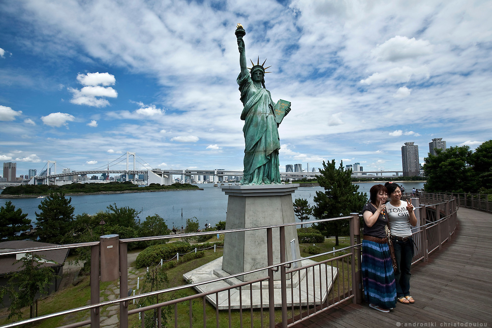 Women posing for a photo n front of the statue od liberty in Odaiba.