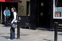 Young woman waiting outside bar in Dublin Ireland, man with baby stroller in background