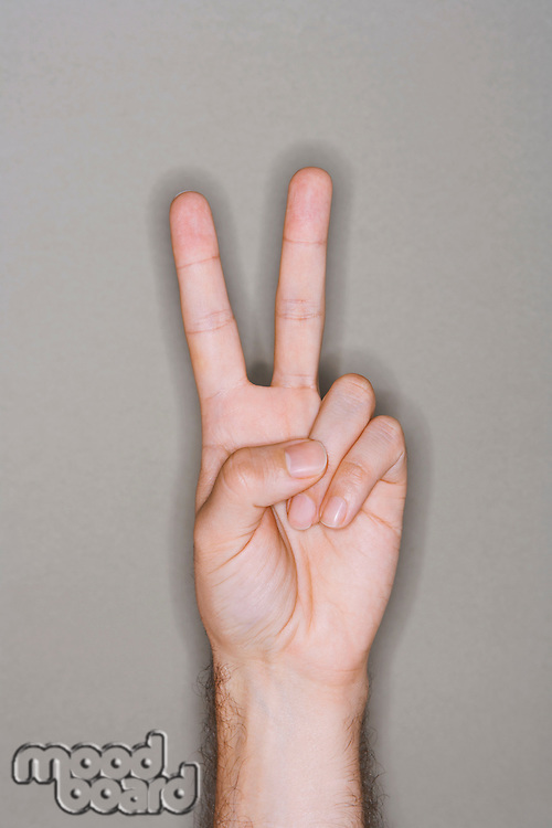 Man making victory sign close-up on hand