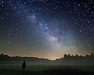 A misty fog covers a field as the milky way shines above. The patches of green in the sky are known as airglow, which is a very weak emission of light by a planetary atmosphere. I couldn't see the green light with my eyes but I could tell from the pictures it was quite active on this night. This self portrait was taken while camping at Sand Ridge State Forest, IL.