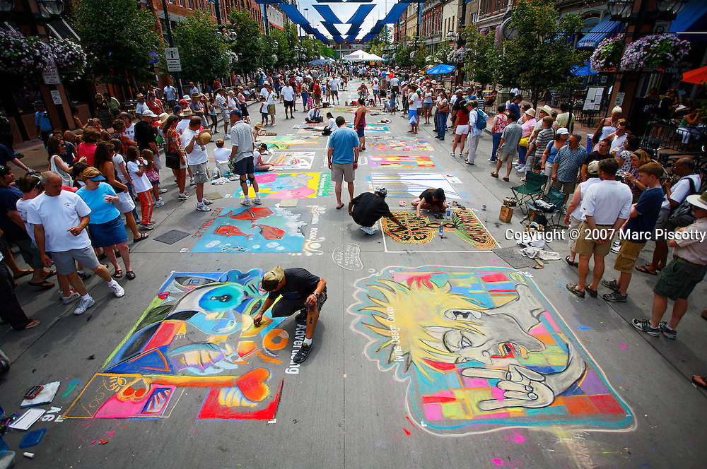 SHOT 6/24/2007 - Street chalk artists work on their individual squares at the 5th annual Comcast La PIazza dell'Arte in Larimer Square in downtown Denver on Sunday June 24, 2007. The streets of the downtown historic district are transformed into a giant canvas as student, amateur and professional artists create temporary works of art on the asphalt. The event follows in the street painting traditions of 16th century Renaissance Italy where madonnari would recreate paintings of the Madonna on the streets with chalk..(Photo by Marc Piscotty/Larimer Square © 2007)