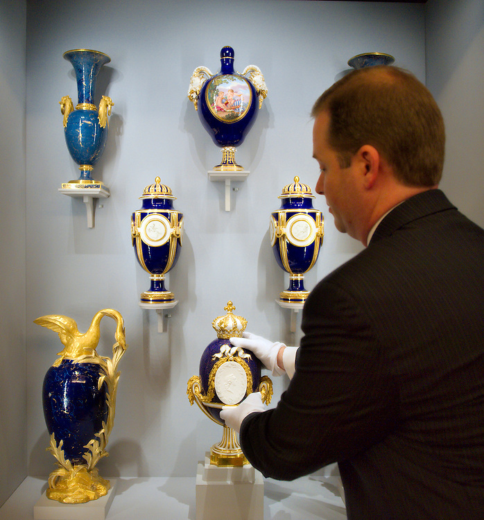 LONDON, ENGLAND - MAY 22:  A  member of staff with a Sevres Vase with Portrait Medallion of Louis XV  on May 22, 2009 in London, England. The Vase is part of the Sevres Exhibition that will open on May 23rd at the Queen's  Gallery  (Photo by Marco Secchi/Getty Images)