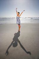 Woman with raised hands standing on beach