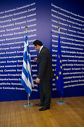 """A European Commission employee installs the Greek flag before the arrival of George Papandreou, Greece's prime minister, at the European Union Commission headquarters in Brussels, Belgium, on Wednesday, March 17, 2010. German Chancellor Angela Merkel said the European Union must avoid any """"overly hasty"""" aid pledge to Greece. (Photo © Jock Fistick)"""