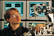 Looking at Cog's still unfinished head, MIT neuroscientist Brian Scassellati ponders where he should mount the microphones that will enable the robot to hear. As important as controlling how the robot responds to people, he believes, is having some control over how people respond to the robot. The project does not have the resources to create a mock human being. MIT, Cambridge, MA. From the book Robo sapiens: Evolution of a New Species, page 65.
