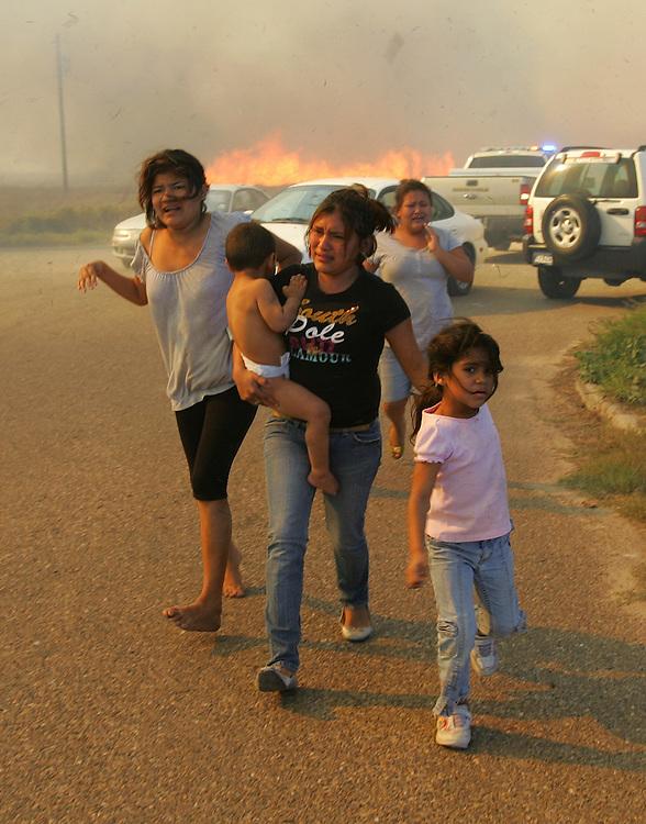 Alton, TX - 19 Jan 2009 - An Alton family evacuates their home on Everest St. north of Alton on Monday afternoon as flames from a rapidly spreading grass fire close in.