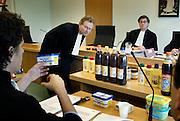 Nederland, Arnhem, 15-4-2005..Een advocaat van Albert Heijn bekijkt met de rechter een kuipje Bleu Band, vastgehouden door een advocaat van Unilever. Rechtszaak gaat over de verpakking van het AH huismerk. Die zou te veel lijken op die van de A-merken van Unilever, met omzetdaling als gevolg. Merkenoorlog, merkenstrijd, omzet, merkrecht, merkenrecht, multinational, prijzenoorlog. Albert Heijn...Foto: Flip Franssen/Hollandse Hoogte