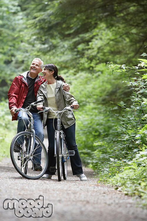 Senior man and middle-aged woman on bicycles in forest laughing