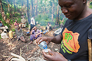 A local man testing the latest batch of plantain whiskey in the Bwindi Impenetrable Forest, Uganda.
