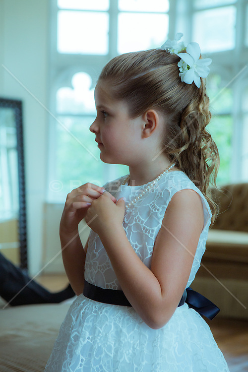 little girl getting dressed for a wedding