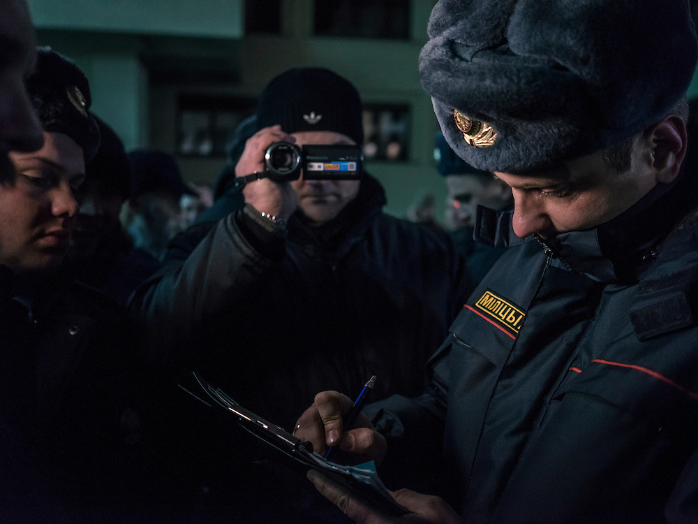 A police officer named Aleksandr Aleksandrovich Kukhta, right, writes a fine for Dzmitry Halko, a translator working for an accredited American photojournalist working on assignment for Al Jazeera America, at a rally organized by Mikalai Statkevich, a former opposition presidential candidate and political dissident, at a rally he organized to commemorate the nineteenth anniversary of a referendum which enshrined authoritarian changes in Belarus's constitution on Tuesday, November 24, 2015 in Minsk, Belarus.