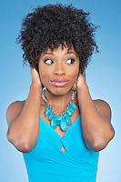 Happy African American woman covering ears over while looking away colored background