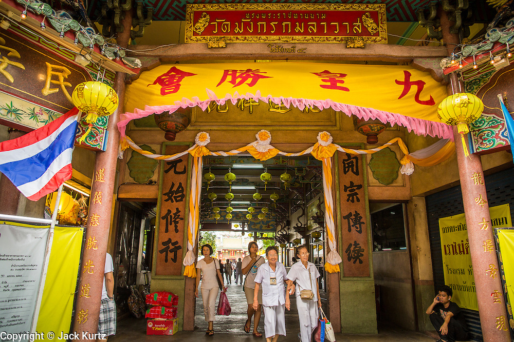 17 OCTOBER 2012 - BANGKOK, THAILAND:   People walk out of Wat Mangkon Kamalawat, one of the largest Chinese shrines in Thailand, during the Vegetarian Festival. The Vegetarian Festival is celebrated throughout Thailand. It is the Thai version of the The Nine Emperor Gods Festival, a nine-day Taoist celebration celebrated in the 9th lunar month of the Chinese calendar. For nine days, those who are participating in the festival dress all in white and abstain from eating meat, poultry, seafood, and dairy products. Vendors and proprietors of restaurants indicate that vegetarian food is for sale at their establishments by putting a yellow flag out with Thai characters for meatless written on it in red.       PHOTO BY JACK KURTZ
