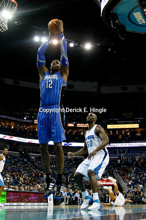 January 27, 2012; New Orleans, LA, USA; Orlando Magic center Dwight Howard (12) rebounds against the New Orleans Hornets during a game at the New Orleans Arena. The Hornets defeated the Magic 93-67.  Mandatory Credit: Derick E. Hingle-US PRESSWIRE