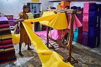 Inde, Rajasthan, Usine de Sari, Les tissus sechent en plein air. Ramassage des tissus secs par des femmes et des enfants avant le repassage. Les tissus pendent sur des barres de bambou. Les rouleaux de tissus mesurent environ 500 m de long. <br />  // India, Rajasthan, Sari Factory, Textile are dried in the open air. Collecting of dry textile are folded by women and children. The textiles are hung to dry on bamboo rods. The long bands of textiles are about 500 metre in length.