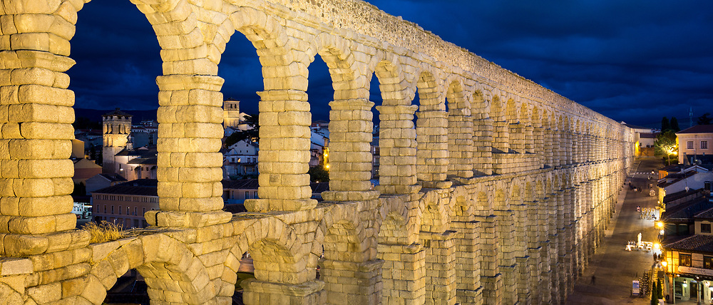 Famous spectacular Roman aqueduct at night, built of granite blocks, by Plaza del Azoguejo, Segovia, Spain
