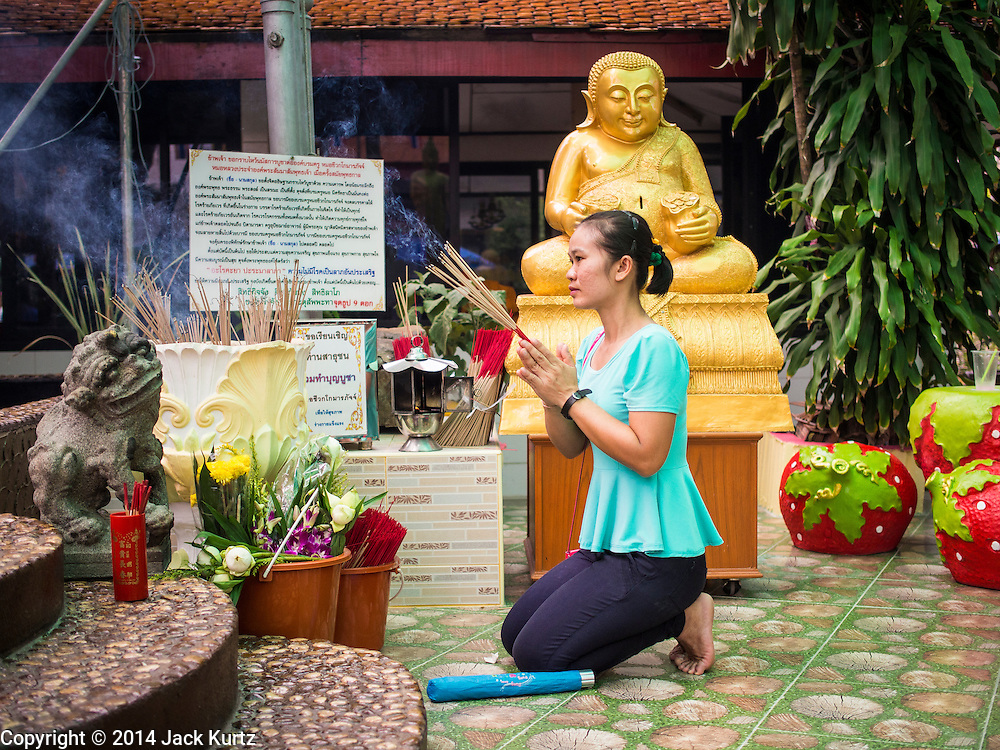 11 JULY 2014 - BANGKOK, THAILAND: A Thai woman prays at an outdoor shrine at Wat Mahabut for Asalha Puja Day. Asalha Puja is the day the Lord Buddha preached his first sermon to followers after attaining enlightenment. The day is usually celebrated by merit making and listening to a monks' sermons. It is also day before the start of the Rains Retreat, the three month period when monks stay in their temple for intense mediation and spiritual renewal.    PHOTO BY JACK KURTZ