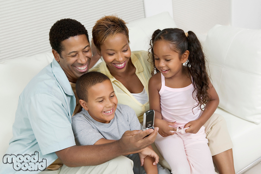 Family sitting on sofa looking at picture on camera phone