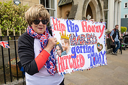 © Licensed to London News Pictures. 16/05/2018. Windsor, UK. Donna Werner, who has travelled from Connecticut in the USA for the Royal Wedding, shows the sign she has made for the wedding day, which reads 'Hip Hip Hooray, Harry's Getting Hitched Today'. Prince Harry and Meghan Markle are to be married on Saturday in Windsor. Photo credit: Rob Pinney/LNP