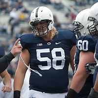Penn State offensive linemen Adam Gress #58, Ty Howle #60 and John Urschel #64 talk to coach Mac McWhorter during warm ups prior to a game against the Illinois Fighting Illini on November 2, 2013 at Beaver Stadium in University Park, Pennsylvania.