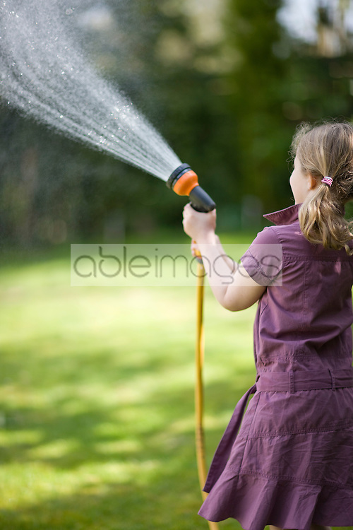 Back of young girl spraying the lawn with garden hose