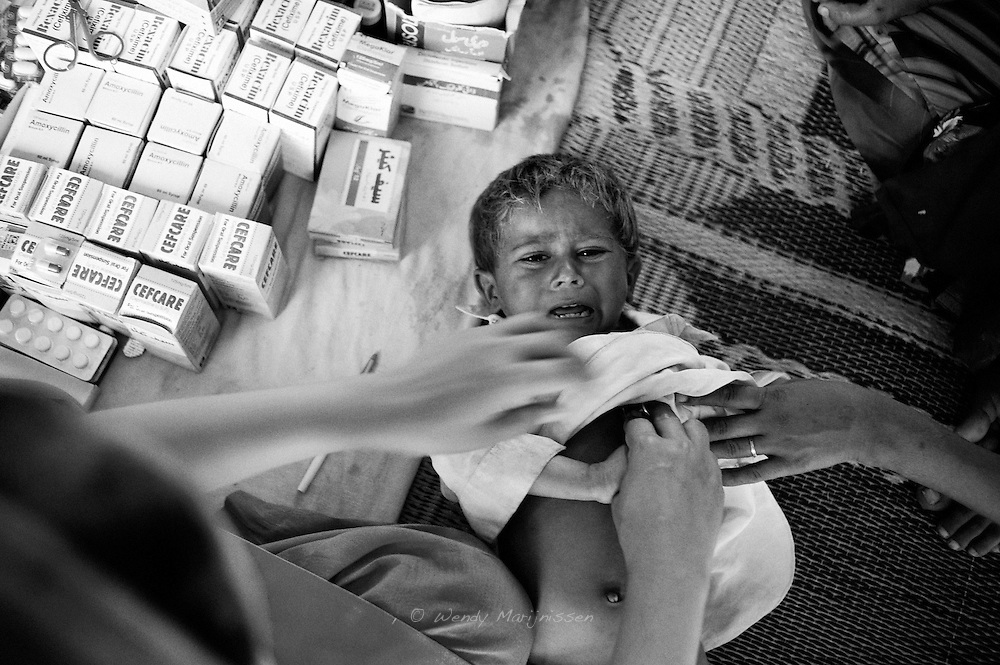 A boy cries when the doctor checks to hear his breath sound. Many of the children in the camps suffer from serious coughs and fevers because of the harsh living conditions. Karachi, Pakistan, 2010