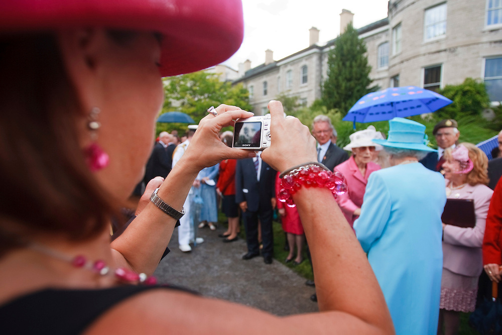 A guest photograph's Queen Elizabeth as she greets attendees at a garden reception  at Rideau Hall, the Queen's official residence in Ottawa, Canada, June 30, 2010. The Queen is on a 9 day visit to Canada. <br /> AFP/GEOFF ROBINS/STR