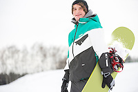 Portrait of handsome young man with snowboard in snow