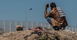 24.06.2016, Dschungelcamp, Calais, FRA, der Dschungel von Calais, im Bild ein Migrant beim Telefonieren. Das Camp ist eine provisorische Zeltstadt nahe der französischen Stadt Calais. Mehrere tausend Menschen kampieren dort in Zeltunterkünften und warten auf eine Möglichkeit zur illegalen Weiterreise durch den Eurotunnel nach Großbritannien. a migrant when making calls. The Calais Jungle is the nickname given to a migrant encampment, where migrants live while they attempt illegally to enter the United Kingdom at the Jungle Camp of Calais, France on 2016, 06, 24. EXPA Pictures © 2016, PhotoCredit: EXPA, JFK
