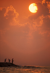 Stock photo of the silhouette of three men fishing from a pier at suset